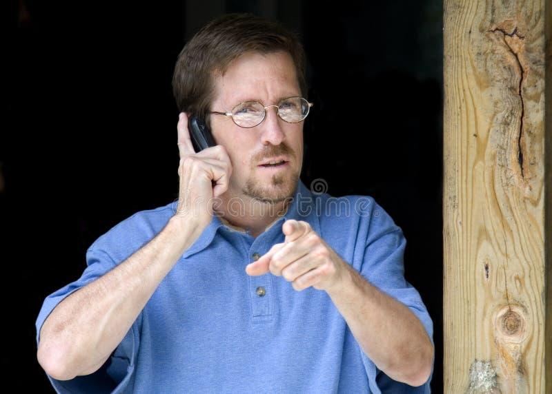 Zeigender Geschäftsmann während am Telefon stockfoto