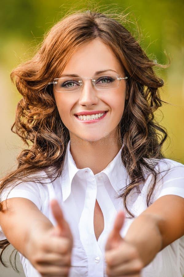 Zeigt reizend Gläser der jungen Frau des Porträts Zeichensieg stockfotos