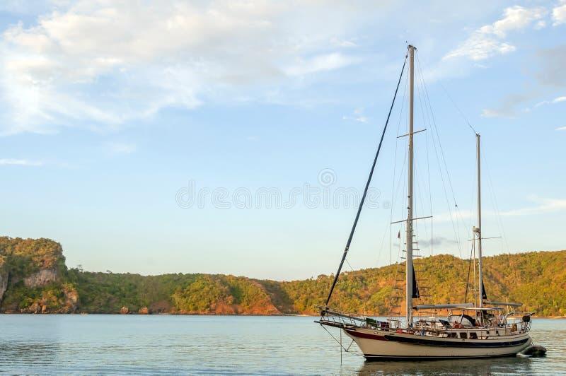 Zeilboot bij ankerplaats in mooie baai bij zonsondergang royalty-vrije stock afbeelding