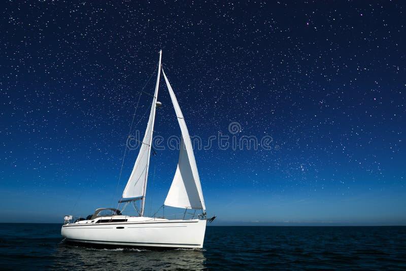 Zeilboot bij nacht met sterren stock afbeelding
