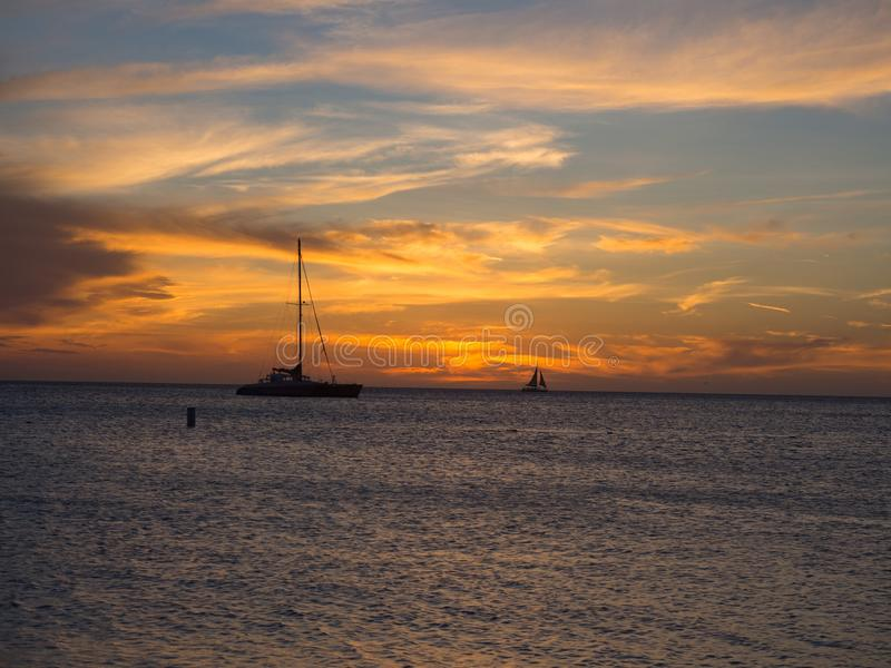 Zeilboot die door een zonsondergang overgaan stock afbeelding
