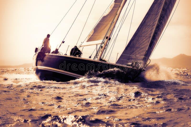 Zeilboot die op zonsondergang varen stock foto's