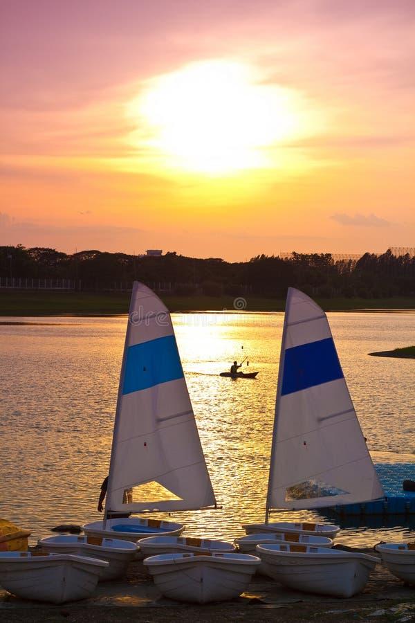 Zeilboot en Canoeing in een mooi meer bij Zonsondergang stock foto's
