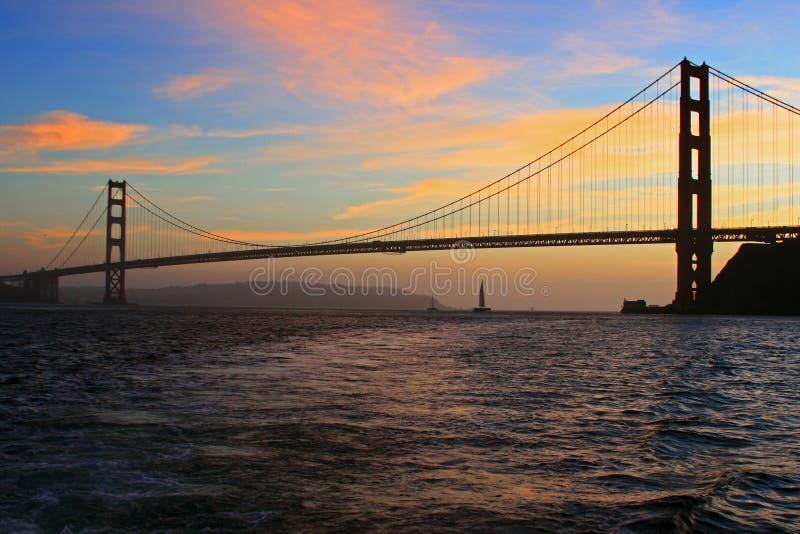 Zeilboot en Golden gate bridge bij Zonsondergang met wolken stock fotografie