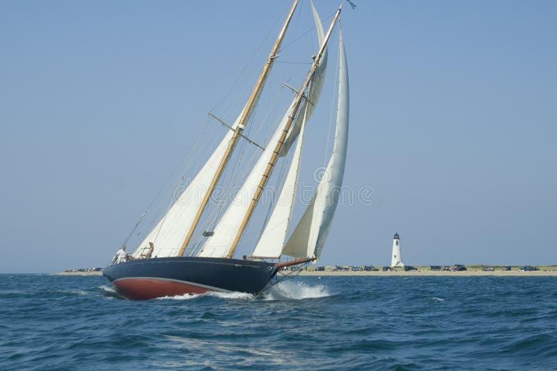 Zeilboot en vuurtoren stock afbeelding