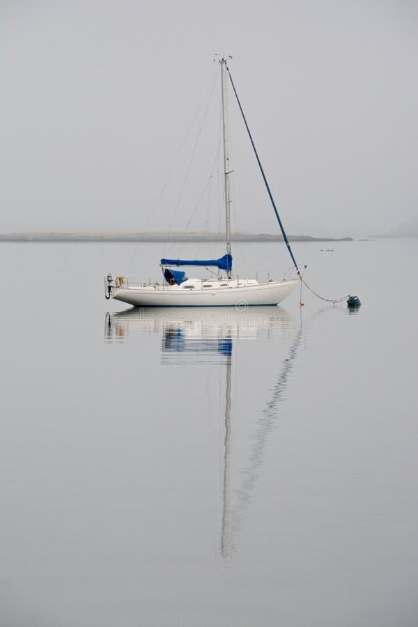 Zeilboot in het water wordt weerspiegeld dat stock afbeeldingen