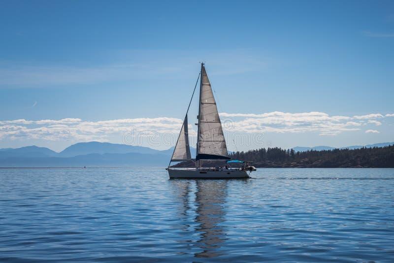 Zeilboot met blauwe hemelachtergronden die bij Vreedzame oceaan varen stock afbeeldingen