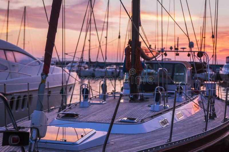 Zeilboot met houten dek die zich in marine bij zonsondergang bevinden stock foto's