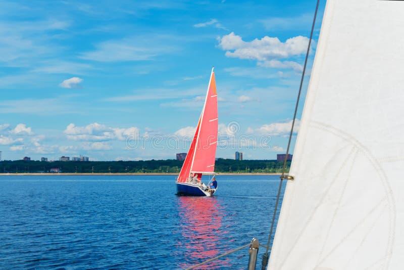 Zeilboot met rode zeilen op de achtergrond van de kust met een stedelijk landschap stock afbeeldingen