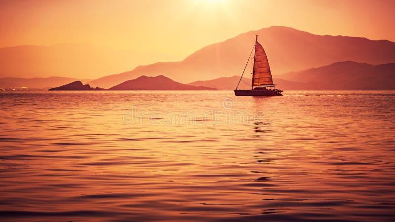 Zeilboot in mooi zonsonderganglicht stock fotografie