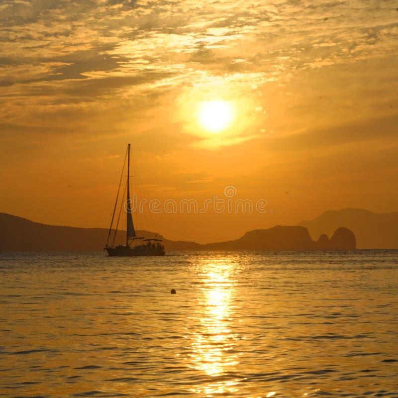 Zeilboot op baai bij zonsondergang stock foto's