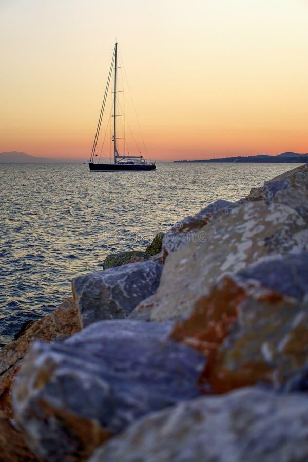 Zeilboot op het overzees bij zonsondergang, rotsen in voorgrond stock foto