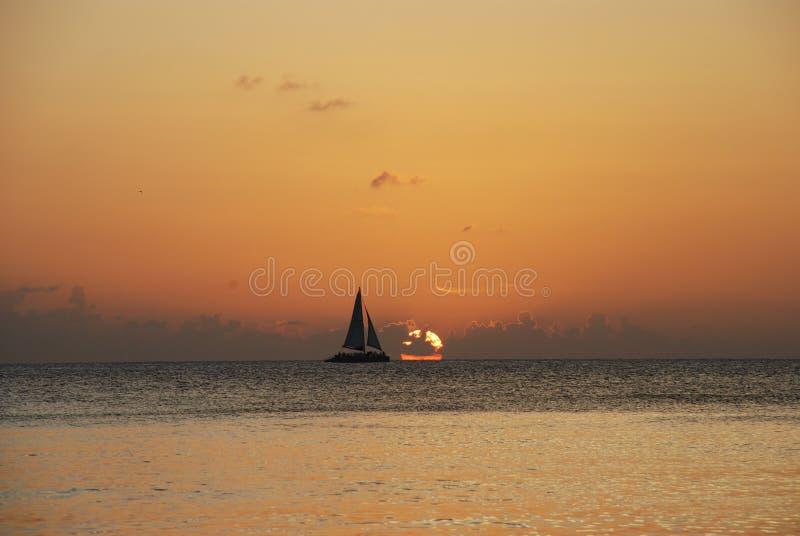 Zeilboot in zonsondergang - Kaaiman stock afbeeldingen