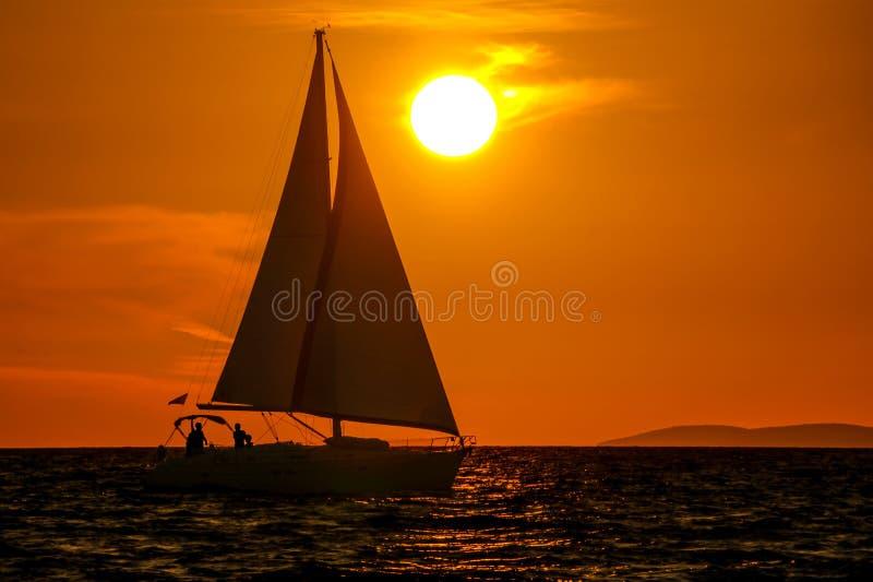 Zeilboot-zonsondergang-oranje hemel stock foto's