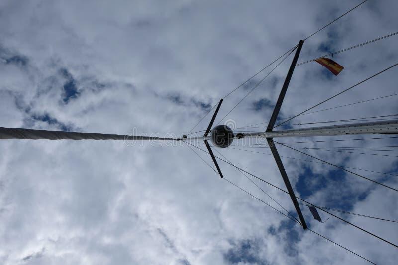 Zeilbootmast met Spaanse vlagmening van onderaan stock fotografie