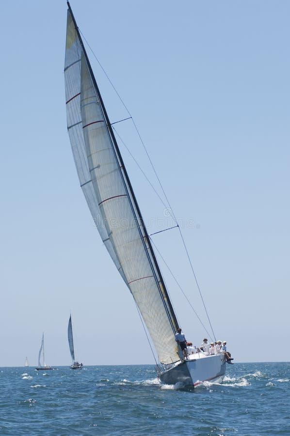 Zeilboten die in de Blauwe Oceaan tegen Hemel rennen royalty-vrije stock fotografie