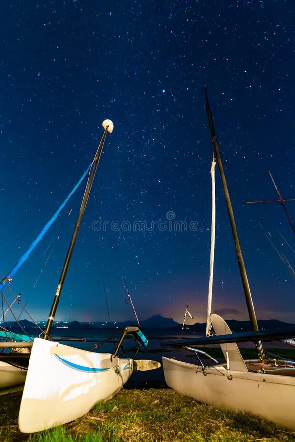 Zeilboten op kust met sterren tegen de achtergrond stock fotografie