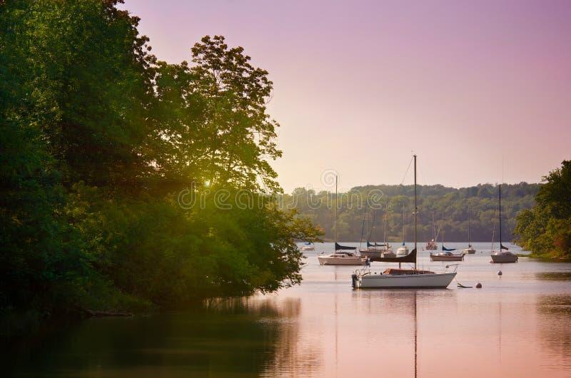 Zeilboten op meer bij zonsondergang stock foto