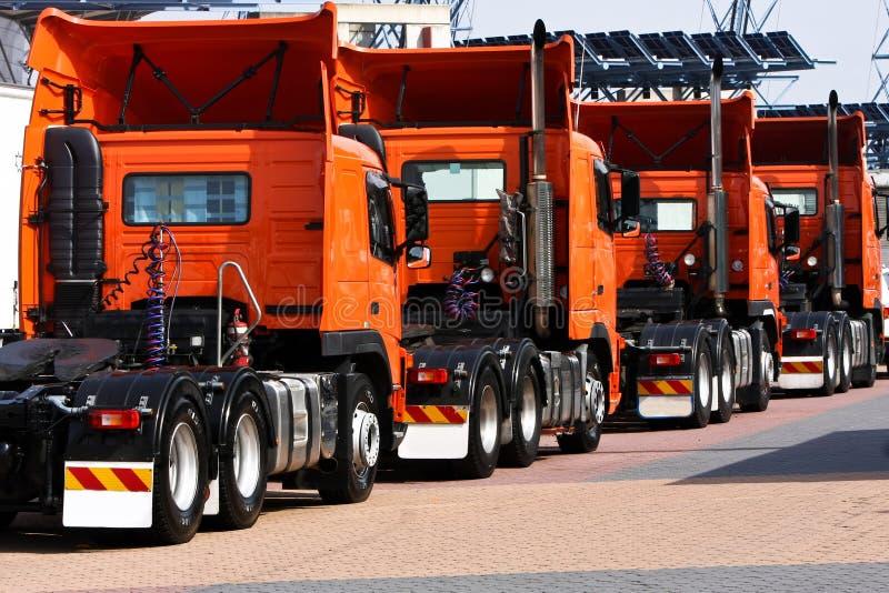 Zeile der schweren Beförderungorangen-LKWas lizenzfreie stockbilder