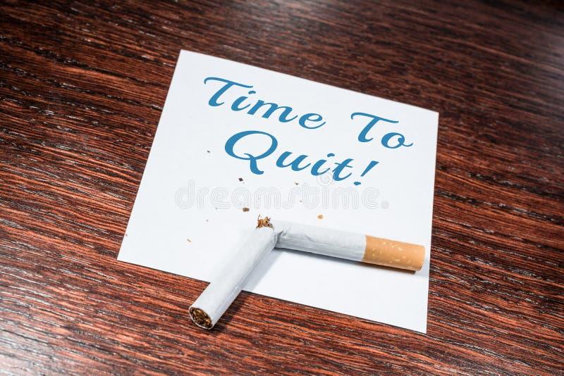 Zeit Anzeige, mit defekter Zigarette auf hölzernem Regal zu rauchen zu beendigen lizenzfreies stockbild