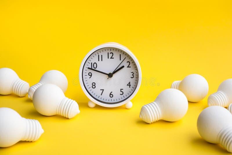 Zeit-, Datumsgrenzen- und Kreativitätskonzepte mit Gruppe der Glühlampe und der Uhr auf Pastellfarbhintergrund Gesch?ftsl?sung le stockbilder