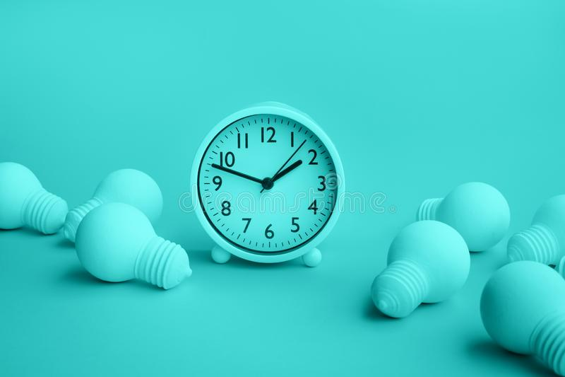 Zeit-, Datumsgrenzen- und Kreativitätskonzepte mit Gruppe der Glühlampe und der Uhr auf Pastellfarbhintergrund Gesch?ftsl?sung le lizenzfreies stockbild