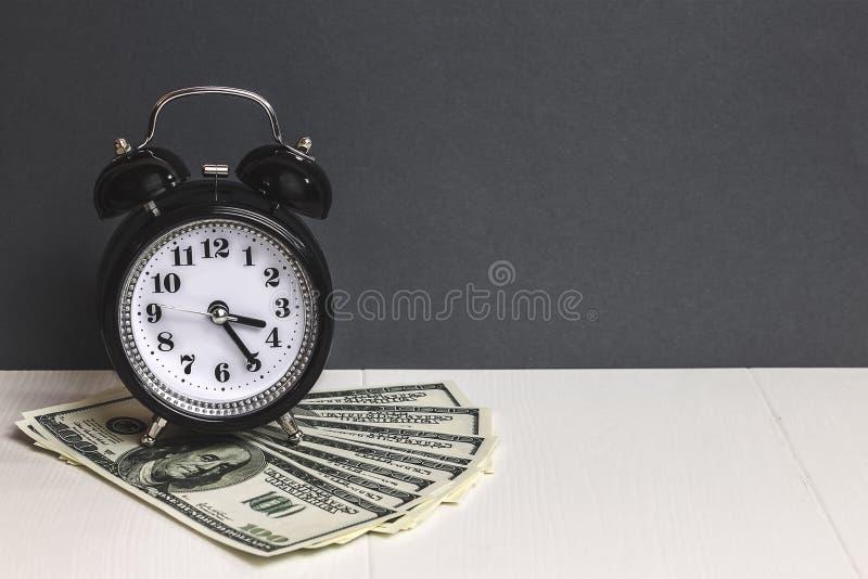 Zeit - ein Geld Dollar Bargeld Retro- Wecker und Bargeld auf Tabelle lizenzfreie stockbilder