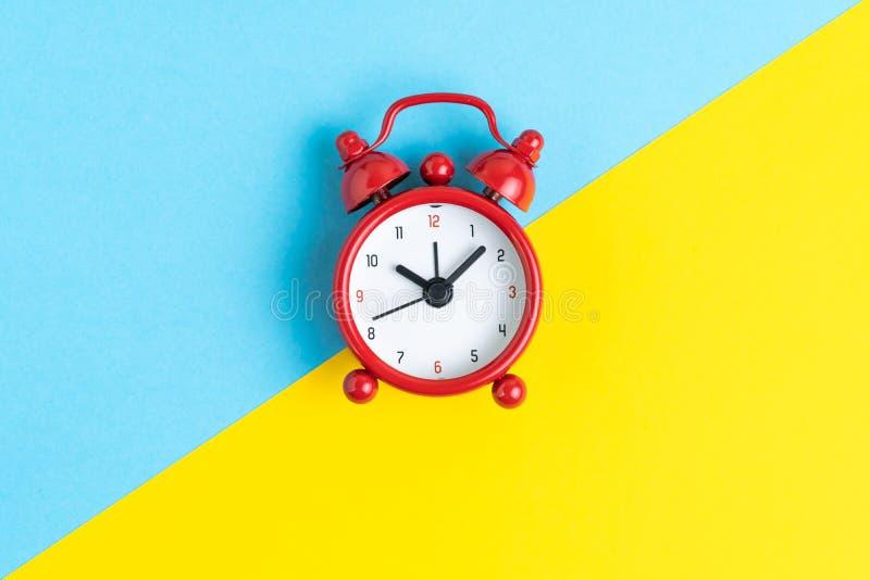 Zeit, Frist oder Timer und Anzeigenkonzept, flache Lage des roten Retro- Weckers auf der Kontrastfarbe gelb und blau Hintergrund lizenzfreie stockfotografie
