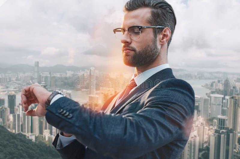 Zeit, Geschäft zu tätigen Hübscher bärtiger Geschäftsmann in der klassischen Abnutzung, die seine Uhr bei mit draußen stehen betr stockfotografie