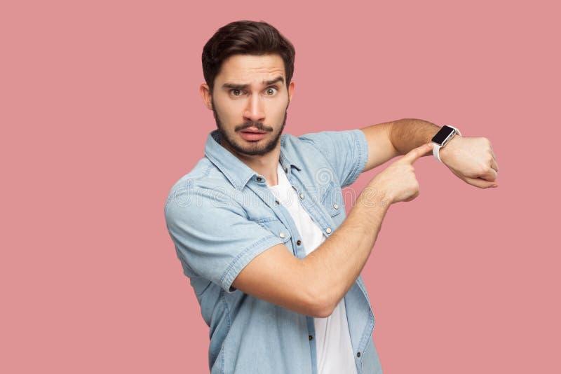 Zeit ist heraus Porträt des ernsten hübschen bärtigen jungen Mannes im blauen Hemd der zufälligen Art, das Kamera, an zeigend ste stockfotografie