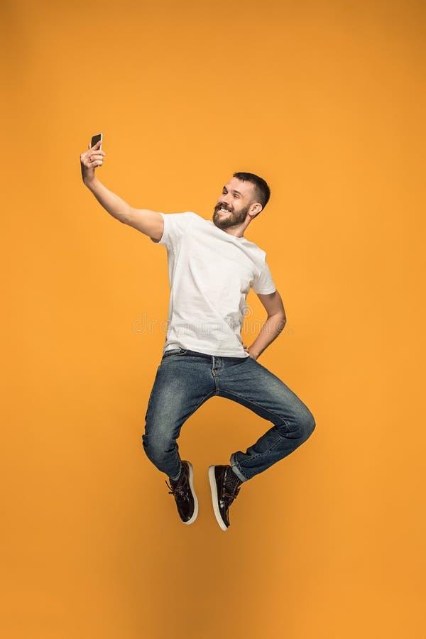 Zeit, selfie zu nehmen In voller Länge vom hübschen jungen Mann, der selfie beim Springen nimmt stockfoto