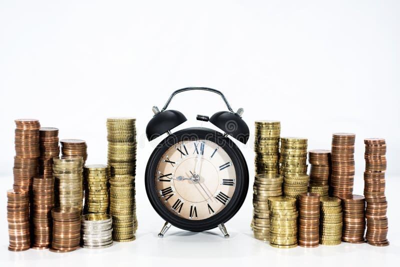 Zeit und Geldabstraktion Viele Münzen mit eleganter schwarzer Uhr stockbild