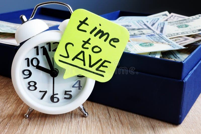 Zeit zu sichern Wecker und Geld auf einem Schreibtisch lizenzfreies stockbild