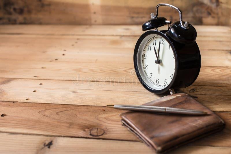 Zeit zum Zahlungskonzept Retro- Glockenuhr Zeit festgesetzt bei 11 O-` Uhr auf hölzernem Hintergrund lizenzfreies stockfoto