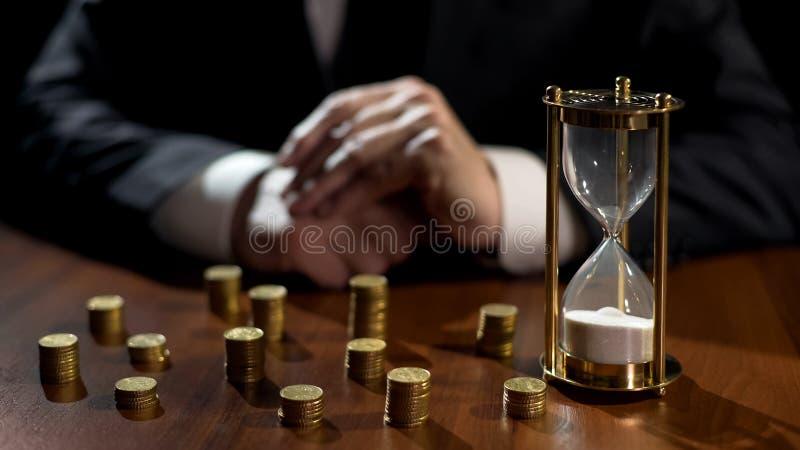 Zeiten oben in der Sanduhr, Geschäftsmann zählt finanzielle Verluste nach Investition lizenzfreie stockbilder