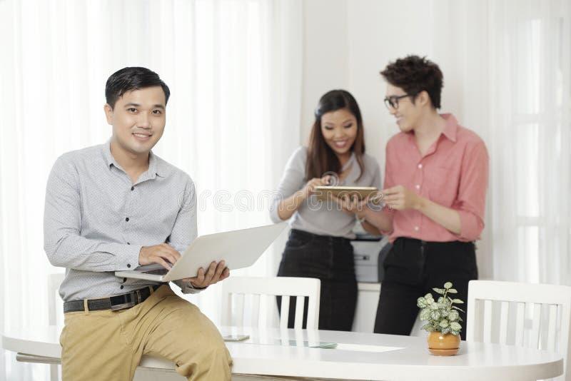 Zeitgenössischer ethnischer Mann mit Laptop im Büro lizenzfreies stockbild