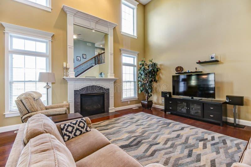 Zeitgenössischer großer Raum mit Kamin und Einbautenspiegel stockbild