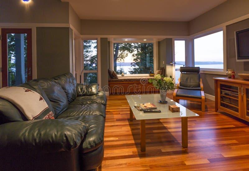 Zeitgenössischer hochwertiger Hauptwohnzimmerinnenraum mit Ledercouch, Glascouchtisch, Fensterplatz und Fenstern mit Wasseransich lizenzfreies stockbild