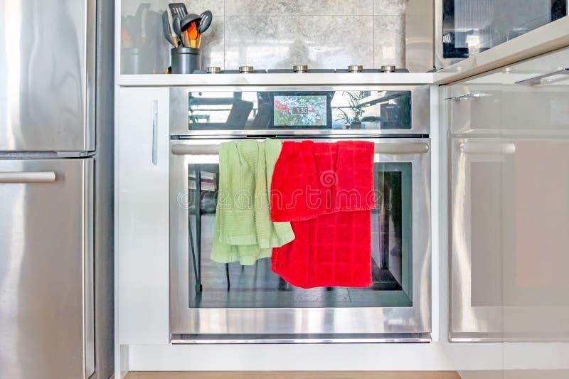 Zeitgenössischer, moderner Chromofen und Ofenstrecke, wenn Farbbildschirmuhr und die grünen und roten Geschirrtücher am Ofen häng lizenzfreies stockbild