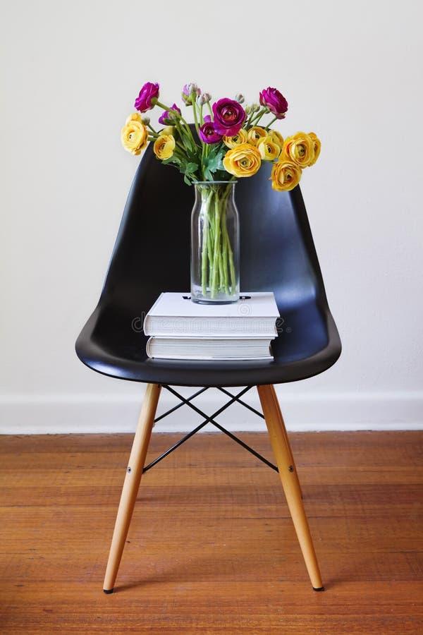 Zeitgenössischer schwarzer speisender Stuhl mit den gelben und purpurroten Blumen stockfotografie
