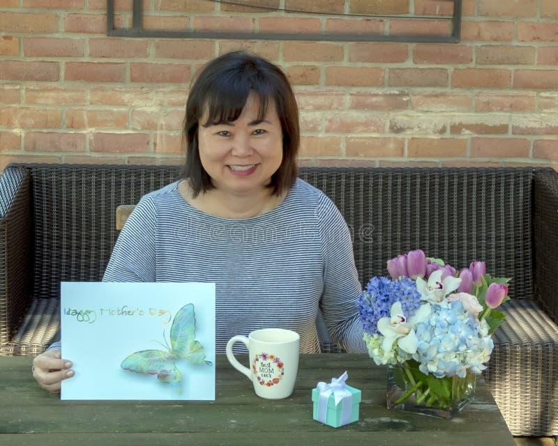 Zeitlose asiatische Mutter, die Muttertag mit Blumen, Karte und einem Überraschungsgeschenk im Kasten feiert stockfotos