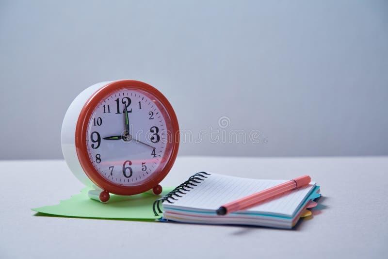 Zeitmanagement, Frist und Zeitplankonzept: Wecker und Notizbuch auf blauem Hintergrund lizenzfreie stockfotos