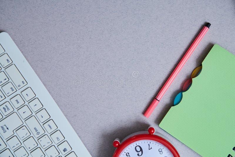Zeitmanagementfrist und Zeitplankonzept: Uhr, Notizbuch und Tastatur auf grauem Hintergrund Flache Lage stockfotografie