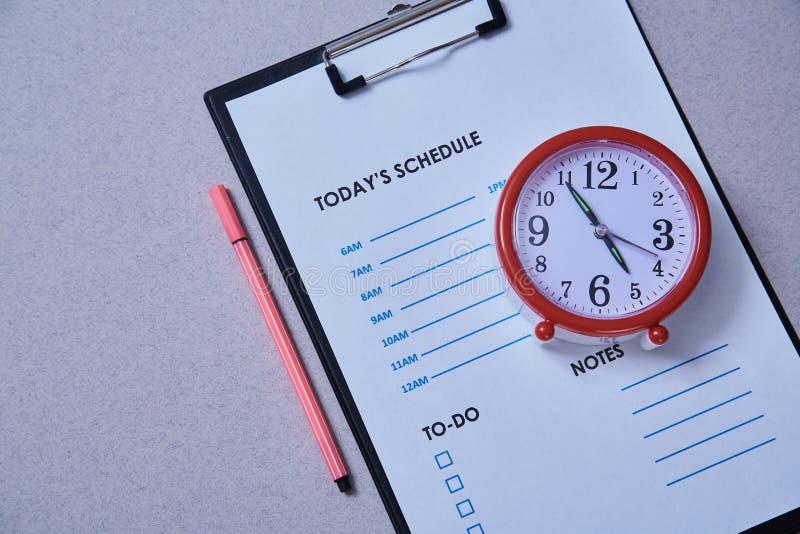 Zeitmanagementfrist und Zeitplankonzept: Wecker auf dem Hintergrund des Zeitplanes stockfotografie