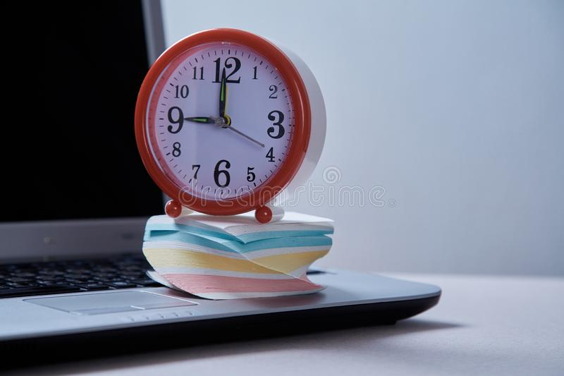 Zeitmanagementfrist und Zeitplankonzept: Wecker und Laptop und klebrige Anmerkungen lizenzfreie stockbilder