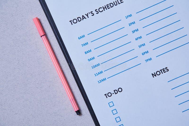 Zeitmanagementfrist und Zeitplankonzept: Zeitplanblatt und -stift auf grauem Hintergrund lizenzfreie stockfotos