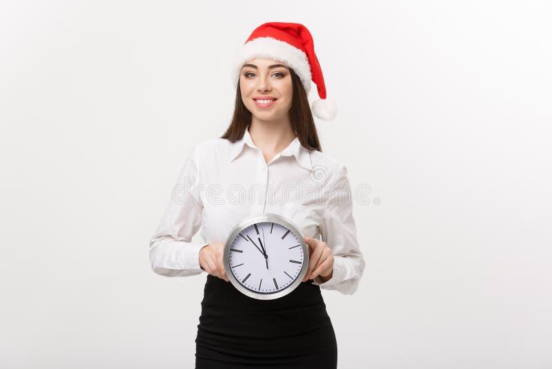 Zeitmanagementkonzept - junge glückliche Geschäftsfrau mit Sankt-Hut holdinga Uhr lokalisiert über weißem Hintergrund lizenzfreies stockfoto