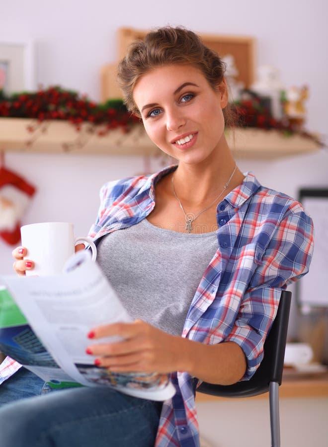 Zeitschrift der jungen Frau Lesein der Küche zu Hause stockbild