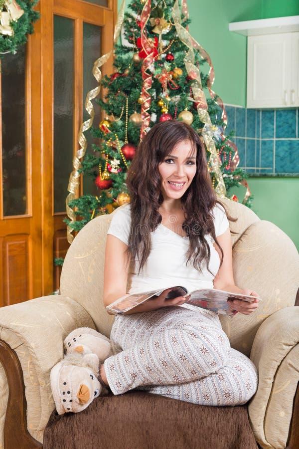 Zeitschrift der recht jungen Frau Lese, dieauf dem Sofalächeln sitzt stockfotografie