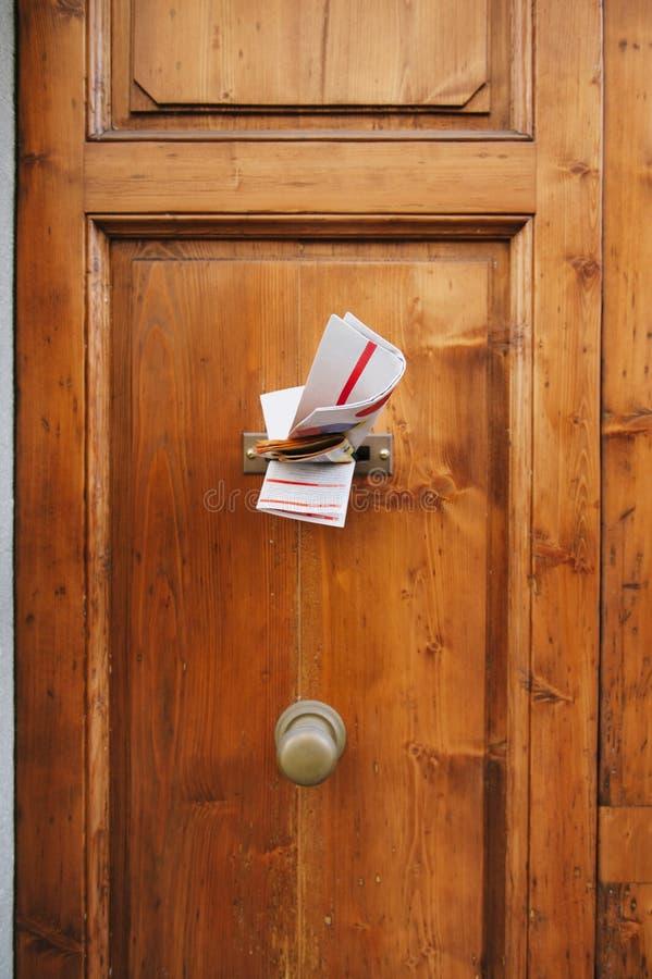 Zeitschriften in einem Briefkasten einer Tür lizenzfreie stockbilder